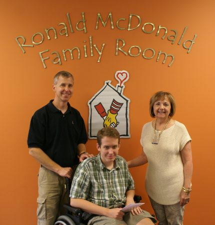 Teen boy in wheelchair with parents